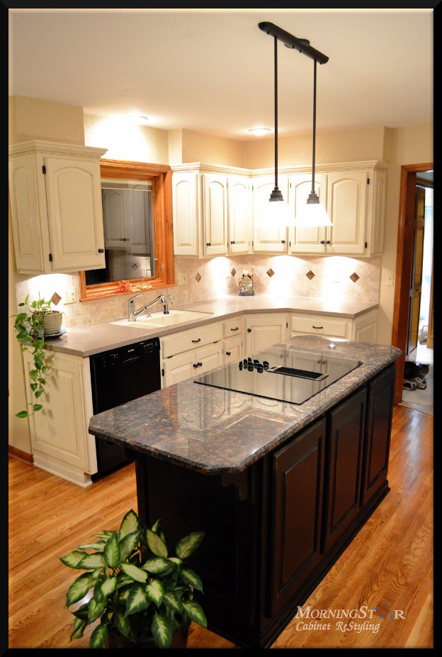 Off-white painted and glazed kitchen cabinets with a black refinished island.