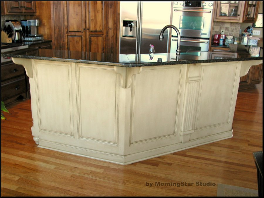 Island cabinet refinished in off white and a medium glaze to bring out the architectural details.